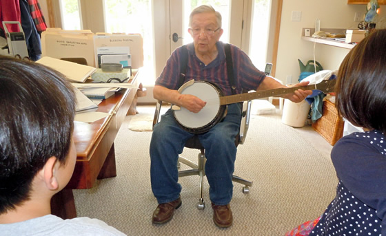 Grandpa plays the banjo and sings a folk song.