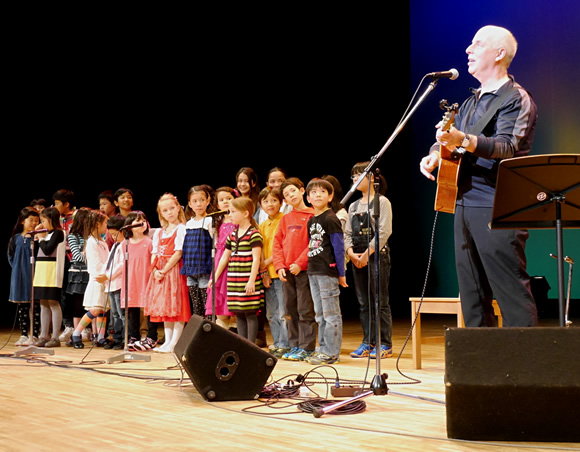 Bill Harley performs with children in Hiroshima.