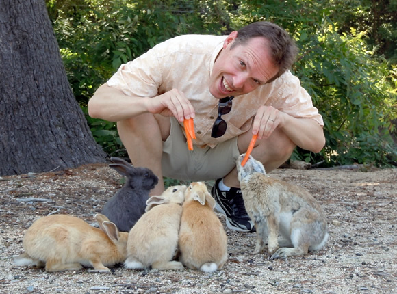 Adam feeds friendly rabbits.